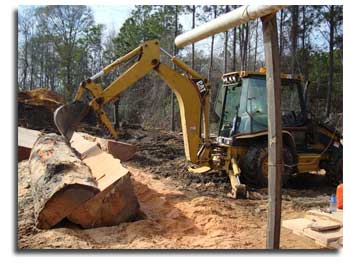 Using our backhoe to help split and over sized log into a managable size.
